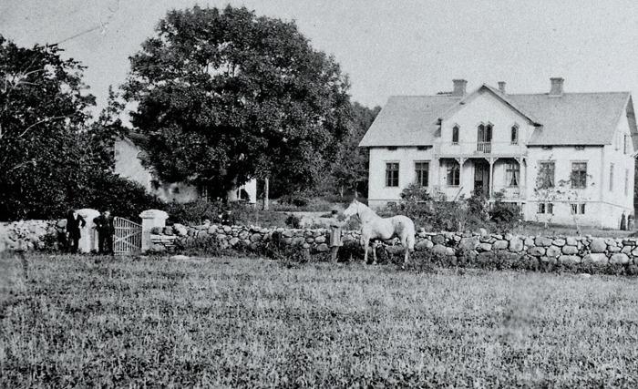 """A. 4 (1) Ulunda ca 1880. Vid tiden ägdes Ulunda 3/4 mtl av Rådmannen Anton Kjellberg, Sköfde. Hans son Gustaf Samuel Laurentz Kjellberg, född 1838, arrenderade gården av fadern, gift med Hilda Elisabeth Westman, född 1843 och sönerna Carl Emil, född 1868 i Varnhem, samt Gustaf Henning, född 1866 i Stockholm. Troligen står delar av familjen Kjellberg innanför grinden. Gården 3/4 mantal såldes 1881 till rektor E. Jungner i Skara. Åren 1885-87 ägdes Ulunda av fabrikör Nils Lundberg. Hans dotter Hedvig Lundberg, som då var i 10-årsåldern skicakde fotot till hembygdsföreningen 1961 med följande upplysningar: """"Mannen som håller i hästen är Pettersson och var bror till föregående ägaren till Ulunda. Han var bosatt i Fiskaregården his sin syster och svåger Jonas Andersson."""" Insatt av Kent Friman, 2014-02-17."""