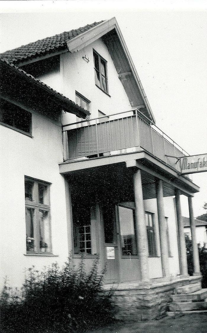 """A. 35 (1) Fastigheten Gärdhem med affär i bottenvåningen och två hyreslägenheter på vindsvåningen. Enligt uppgift lär huset vara byggt av virke från rivna byggnader vid Skaraborgs regemente i Axvall. Husen med uthus brann ner i Varnhemsbranden 1979. Gärdhem med Manufakturaffärskylten för Lisa Larssons """"korta varor"""" och inlämning av kemtvätt. Gärdhem som var """"Lisa Larssons"""" Manufakturaffär fr o m 1940-talet """"Mode-Lisa"""" kallad - byggt 1914 som Slakteributik av slaktare Olof Josef Johansson Sjöholm från Skövde - se ovan! Affären hade många """"korta"""" varor och undertecknad minns de små utfärderna med systern från hemmet något hundratal meter bort vid stationsvägen, för att köpa Mors-dagspresenter. Ofta räckte pengen till någon enkel maskinsydd duk eller set med spetsförsedda näsdukar eller liknande. Affären hade allt för hemsömnad och färdiga klänningar i rätt mode och andra kläder för kvinnor och """"Mode-Lisa"""" var omtyckt för sin fina affär. Affären med Lisa deltog alltid också i den skyltsöndagsuppdukning som gjordes inför första helgen i advent. Alla Varnhemsbor var troligen ute på detta """"event"""" med de olika affärernas försök att överträffa varandra i fina och juliga skyltfönster inför julhandeln. På 1960-talet Konsum, """"Lisa-Larssons"""" och Österlunds affär; """"Anton Larssons eftertr."""" Affären Nydal skymtar i bakgrunden till höger. Insatt av Kent Friman, 2014-02-18. Läs mer på www.saj-banan.se!"""