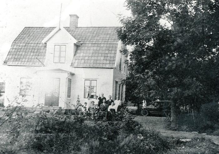 A. 36 (1) Knut hade utvecklat verksamheten och installerade en bensinpump nära landsvägen mellan Skara - Skövde. På bilden ses en bil parkerad vid pumpen under träden mot vägen. Familjen Ohlosson är samlad för fotografering på den västra delen av huset nära södergaveln. Knut och Meli i mitten med sönerna på var sin sida av mamma Meli, samt Melis mor vid Knuts vänstra sida. Bilen tycks visa att detta är någon gång under 1930-talet. Huset och träden är helt borta sedan den stora Vanhemsbranden då 21 hus brann ner 1979 och man röjde för att bygga nytt. Det syns på bilden att man just skapat en inkörningsväg in framför gaveln mot vägen för tankning. Dörr för ingång till Caféet kan ses på gaveln redan här (nedsänkt karm) - jämför foton nedan! Insatt av Kent Friman, 2014-02-24. Läs mer på www.saj-banan.se!
