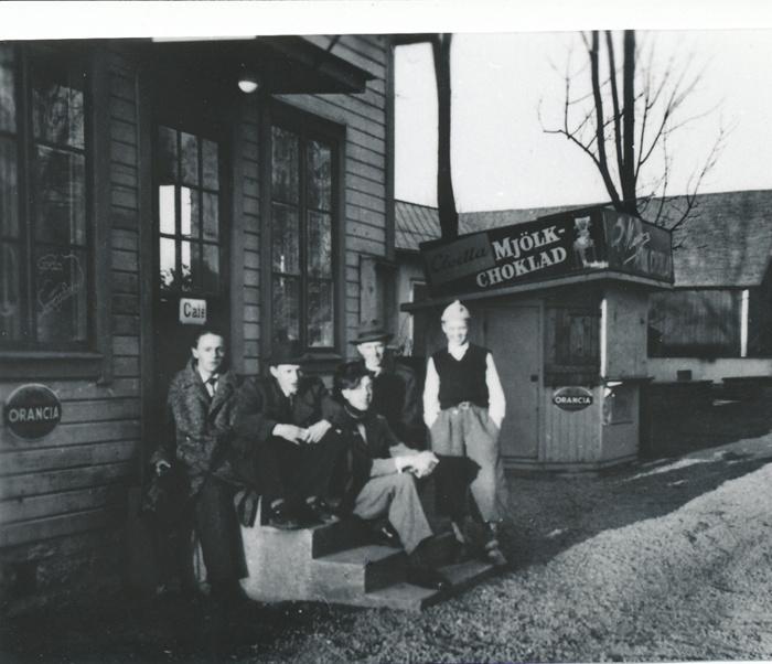A. 36 (2) Runhem knappt 30 år gammalt, 1954, några år efter att Erik och Edth Petterson köpt fastigheten - men i ursprungsskick med trappa och kiosk. De byggde snart till en del för utvidgning av caféet mot öster, bakom kiosken på bilden. Några av de unga Varnhemsborna på den tiden samlade på trappan till Caféet med goda smörgåsar och annat gott annonserat på fönsterrutorna. Cloetta mjölkchoklad och Marabou mjölkchoklad fick båda plats med reklamskyltar på taket till kiosken. I bakre raden skall enligt dottern Roland Johansson finnas iklädd mössa. Insatt av Kent Friman, 2014-02-24. Läs mer på www.saj-banan.se!
