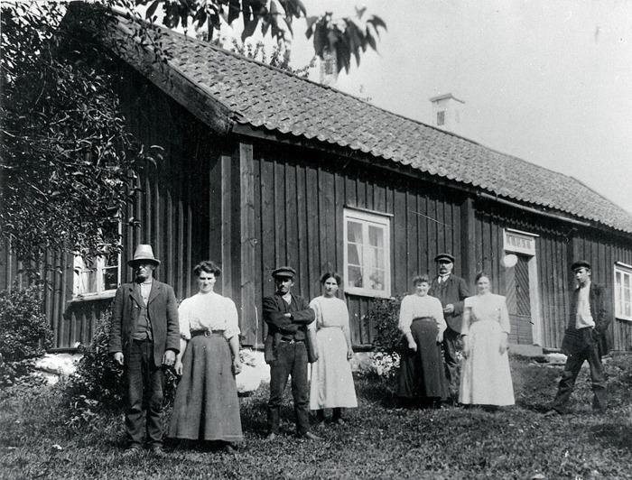 """A. 31 Ivarstorps mangårdsbyggnad. Foto från före 1920 då verandan byggs till. Ivarstorp är ett av sockenen äldsta bostadshus. Gården var ursprungligen ett Kronohemman, vars ägare var skyldig att bidra till rusthållet frö den indelte soldaten i Stenslund. Det kallades för """"Kronoskatte Augementshemman"""". Ivarstorp friköptes från Kronan 1759. Man tror att nuvarande huvudbyggnad tillkom då.Från vänster på bilden August och Eugenia Jonsson (dåvarande ägare i 2:a giftermålet), Oskar Jonsson (son i första giftermålet), Jenny Jonsson (dotter 2:a giftermålet), Alida Jonsson (syster till August - (bräcklig) och familjen Juhlin från Stockholm, dvs Erik Johan Juhlin, Augusts syster Kristina Juhlin, samt deras son Conrad Juhlin - t h. Juhlins tyckte om att vara på Ivarstorp under somrarna. (Uppgift Bengt Jonsson, Oskars son) (Bild från Varnhemsbygden 2005, artikel Alf Hansson) August och Eugenia Jonsson hade då varit gifta sedan 1899. Augusts första fru, Elin Sofia Pettersson, född 1869 den 30/9, ingick han giftermål med 1891 den 5/5, och hon dog endast 27 år gammal 1897. De levde tillsammans i drygt 5 år och giftermålet tog plats exakt ett år efter att sonen Oskar fötts. Oskars far var 43 år gammal gammal när hans unga (27 åriga) maka dog och Oskar endast 7 år. Fadern, Johan August Jonsson, född i Varnhem 1854 den 12/8, gifte sedan om sig 1899 den 1/10, tre år efter fruns död, med pigan Eugenia Holmberg född i Varnhem 1882 den 3/2. Hon flyttade in som piga på gården 1897 den 3/11 (15 år gammal) och de fick dottern Jenny Karolina Jonsson 1898 den 30/12, då hon var 16 år gammal och Eugenia var vid giftermålet 1899 17 år gammal - August var då 45 år gammal och sonen Oskar från första giftermålet alltså 9 år. Sonen Oskar övertog gården 1924, när han gifte sig med mjölnarens vid Hålltorps kvarns dotter, Anna Berg - se rubriken A. 10 Hålltorps kvarn. Fadern August dog 1926, i sviterna efter en hjärnblödning några år tidigare. Insatt av Kent Friman. 2014-02-24. Läs mer på www.ljungstor"""