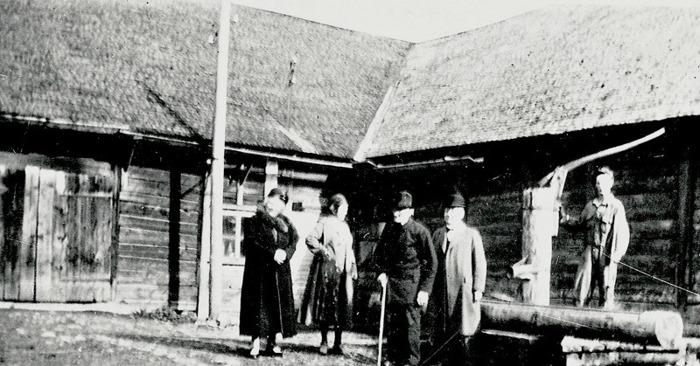 A. 10 (1) Bild från fägatan/ladugårdsplan vid Hålltorps gamla ladugård 1936. Till vänster står Petter Lindqvists sonsons hustru. Per August Petterrson med käppen och sonen Arvid. Vid pumpen står drängen Helmer Alm, då 17 år gammal. De finklädda skall just på resa till Bäckedalen och Petter Lindqvists gamla hus i Ljungstorp, där Per gick i skola som liten hos privatläraren Petter och var två år yngre än Petters egen son Johan, som var Pers livslånga vänskap. Se bild A. 32 (1) med sällskapet på Bäckedalenhuset! Insatt av Kent Friman, 2014-03-05. Läs mer på www.ljungstorpshistoria.se!