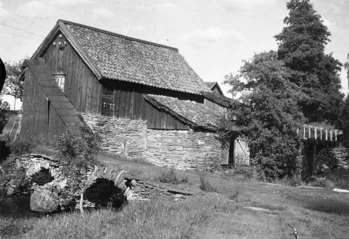 """A. 12 Bille kvarn 1930. Den södra sidan av Bille Kvarn 1930 med den dubbla stenvalvsbron, inbyggt kvarnhjul och med stenunderbyggd kvarnränna och damm. Foto Nils Lann, Ljungstorp/Varnhem. I dagligt tal kallad """"Spetarskvarna"""", en dialektal form av """"Hospitals kvarn"""". I 1699 års jordebok är anteknat """"En kvarn vid klostret"""" som 1684 är taxerad och anslagen Skara Hospital (sjukhus). I 1726 års jordebok redovisas även """"Bille kvarn"""", anslagen """"Skara Hospital"""". Det har funnits två kvarnar vid platsen, vilket även anges i kartbesrkivningen 1864; """"Norra Qvarn"""" och """"Södra Qvarn"""". I 1825 års jordebok är antecknat att häradshövding Jonas Lundin låtit uppbygga Billekvarn som år 1726 blev Skara Hospital anslagen, vidare att kvarnarna gå med ett par stenar vardera höst och vår, samt att Klostrets kvarn och Bille kvarn sammanbyggts 1823. Båda kvarnarna drevs som tullkvarnar. Sannolikt är kvarnhuset på bilden från 1823. 1916 såldes fastigheten med kvarn av Domänverket till dess arrendator Otto Gustafsson som drev den med 2 par stenar. Sista förmalningen skedde 1 november 1942, då fstigheten sålts till en man Karlsson från Edsvära, vilken sedan rev kvarnen. 1945 uppförde bröderna Rask ett spnneri på platsen. Insatt av Kent Friman, 2014-02-17. Läs mer på www.ljungstorpshistoria.se - under A. 8 a Pickabacken!"""