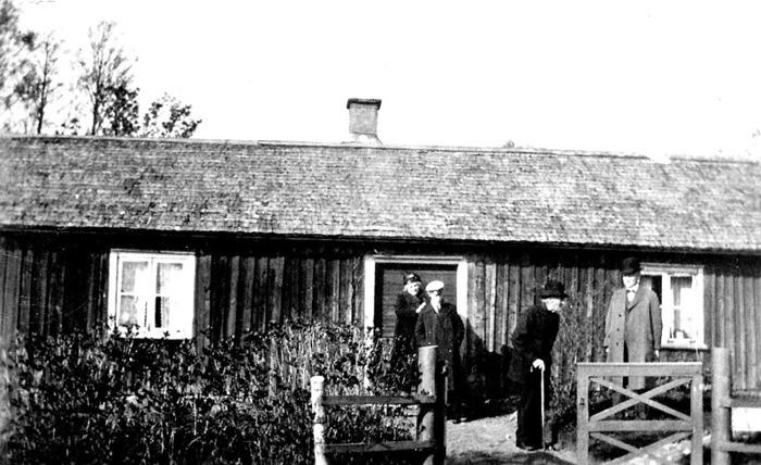 """A. 32 (1) Bäckedalen runt 1930. Gamla stugan i Bäckedalen, där Petter Lindqvist bodde och troligen undervisade skolbarn under 1830-40-talen. På bilden står från vänster Petters sonsons hustru, ett barnbarnsbarn, Per Hålltorp (med käpp) omkring 95 år gammal och Arvid på Hålltorp, son tilll Per. Naturnamnet Bäckedalen kommer sig naturligt av den djupa bäckravin som finns inom området som grundar upp fram emot Ljungstorspsvägen på Flinkebackens mark. Det lär ha funnits en skvaltkvarn nära platsen på Flinkebackens mark - en kvarn för husbehovsmalning. Det finns på karta 1882 en damm-markering på den intäkten. Bäckens ravin har också naturligt skapat gränserna för de många små intäkter och boplatser som skapades här - främst under 1800-talet. Här bodde också David och Josefina Roth (""""Fina""""). Stugan revs 1938 och den nuvarande uppfördes till stor del av timmer från det rivna hemmanet Sten. Insatt av Kent Friman, 2014-02-24. Läs mer på www.ljungstorpshistoria.se!"""