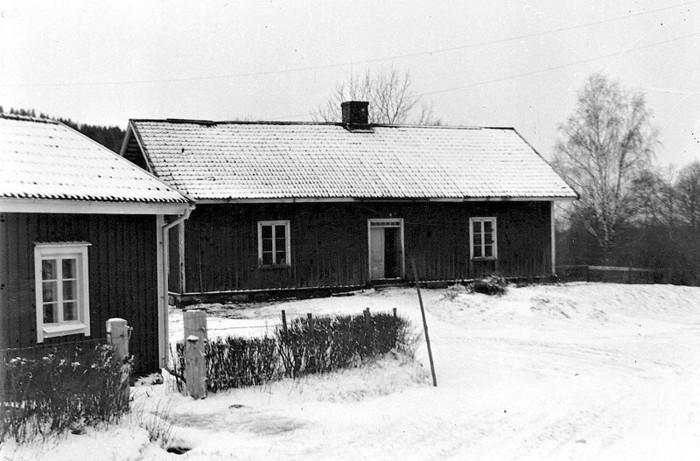 """A. 19 Fattigstugan i Ljungstorp. """"Socknens Fattistöva"""" Varnhems sockens fattighus låg vid Ljungstorspvägen nära nuvarande korsning med vägen från Fermabron och Gamla Kungsvägen (Ljungstorpsvägen). Exakt byggnadsår okänt, troligen ganska snart efter beslutet att bygga huset på sockenstämman 1815, men omnäms inte i husförhörslängd förrän 1836. I huset fanns tre ganska stora rum med en öppen spis i varje som enda inredning samt ett vindsrum. Den som var s.k. föreståndare förfogade över en kammare och ett kök. Vid vänstra hörnet stod en vedbod (syns inte på bilden), vid andra gaveln ett dass. I kammare och köket bodde till 1941 Maria Stina Persson, född 1853*. I östra delen gjordes en enkel upprustning på 1940-talet. De sista som bodde där var fru Signe Sandkvist och hennes tre söner, efter en skilsmässa 1933 från maken som då flyttade till Mariestad. De hyrde Fattigstugan för boende och där bodde också """"föreståndaren"""" alltså kvar. Huset nedtogs 1958-59 och flyttades till Vadet, där det tillsammans med Norra Lundby fattighus uppfördes som hönseri. 1950-tal. Fotograf Nils Lann, Ljungstorp/Varnhem. *Maria Stina Persson, föreståndare fr o m 1909 och den sista tiden. Äldre, minnesgda personer har berättat att de inhysta hjonen förr i tiden fick hämta sin ved på Hålltorp. En bild av forna tiders fattigvård. På 1700-talet låg socknens fattigstuga vid Ännebäcken, enligt forskningar och enligt Nils Lann. Insatt av Kent Friman, 2014-02-17. Läs mer på www.ljungstorpshistoria.se!"""