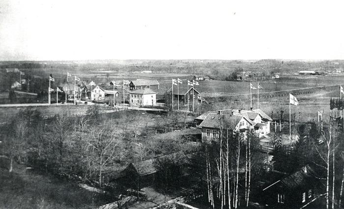 """B. 6 1923 Utsikt från kyrktornet vid återinvigningen av klosterkyrkan efter restauration. De olika affärsfastigheterna i Varnhem grupperade runt järnvägen. Bilden tagen från kyrktornet 1923 inför kungens besök och återinvigningen av klosterkyrkan efter renovering. En renovering där Knut Ohlsson arbetade med takomläggningen av tjärat ekspån åren innan han byggde Runhem - se nedan! Den gamla Bybron över Bybäcken fanns ännu kvar med sina vägräcken och vägen gjorde en svag sväng för att passera bäcken. SAJ-banan mot Skövde hade relativt stora terrasseringar för att hålla nivån fram till landsvägen. Särskilda flaggstänger har sats upp vid bangårdsområdets början efter landsvägen, och på en del andra ställen, inför det celebra besöket av Hans Majestät Konungen. Från vänster (väster); Björsgården (tidigare Gästgivaregården) med mindre affär - se nedan!, Ulfsgården med taxirörelse - se nedan, Eriksdal med Konsum, Gärdhem, Nydal - se nedan, Affären med magsin samt de båda skolorna - den så kallade mellanskolan i Kyrkeparken (se nedan!) och Folkskolan i gamla Klosterdahl (fr o m 1917). Lägg märke till det gamla """"kyrkstallet"""" med offentliga toaletter där Kyrkstigen från järnvägsstationen kom fram till Kyrkogatan. Runhem ligger alldeles utanför bild till höger utmed landsvägen - flaggstången syns! Det ljusa taket längst bort till höger hör till sågen på den s.k. Sågarebacken. Den ägdes av Gustav Andersson på Tomten och sedan av sonen Allan Stålheim. Sågen drevs av en lokomobil och här utfördes legosågning vinter och vår, mest för bygdesn folk. Sågen revs 1959 då den nya vägen drogs fram här! Obs! Anledningen till att den svenska flaggan på fotografier från 1800-talet och början 1900-talet ser ut att vara vit med ett mörkt kors är att den fotografiska filmen och glasplåtarna hade en ortokromatisk emulsion som var okänslig för rött (rött blev svart), och mycket känslig för blått. Orange och gult blev mörkare än normalt, medan blått blev mycket ljust. Insatt av Kent Friman, 2014-0"""