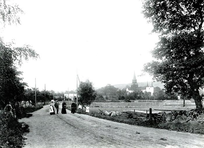 """B. 7 (2) Endast digital bild! En bild väster om järnvägsövergången med Skara-Skövdevägen i Varnhem vid samma tidpunkt som översiktsbilden från kyrktornet ovan, dvs 1905. Virkesupplaget syns på andra sidan järnvägen - troligen för bygge av bl a staketet till SAJ-banan. Likaså kan man skymta nedtagningsvirke från den pågående nedtagningen av Junkragårdens ladugård i bildens högra hörn. (Bild från Västergötlands Museum - bildarkivet/bildnummer: A122005:A) Vägen till stationen har en anslutning till Skara-Skövde-vägen på bilden före järnvägsövergången från betraktarens håll - i gränsen mot Junkragårdens mark. De ljusa svagt skymtande bommarna för vägövergången kan ses bakom familjen ett stycke bort, liksom staket utmed järnvägen och det finns även en svag skymt av affären - jmfr bild här! Fotograf Karl Fredrik Andersson, utbildad av Ludvig Ericsson, Skövde (som tog fotot från kyrktornet ovan vid samma tid!). Utbildningen varade ett år mellan oktober 1893- oktober 1894. Han var verksam mestadels från bostaden i Skultorp och dog 1949. Bildberättelse kring bilden ur """"DOKUMENT I SVART OCH VITT - ett urval av fotografen Karl Fredrik Anderssons bilder från Västergötland med kommentarer av sonen Karls-Anders Andersson"""". Tryckt 1981: """"Veterinären Sjöstrand från Upphärad med hustru, barn och svägerska söndagsflanerade i närheten av Varnhems klosterkyrka med Billingsberget som avlägsen fond. Den grusbelagda landsvägen hade ännu sin gamla sträckning genom Varnhem. Den bär på bilden inte några spår av bildäck, är ännu helelr inte direkt sönderkörd av tunga vagnshjul, som landsvägarna brukade vara, men den är rik på högar av hästspillning, vilket vittnar om vem det var som stod för förflyttningsprestationerna före de bundna hästkrafternas tid."""" Insatt av Kent Friman, 2014-02-25. Läs mer på www.saj-banan.se!"""