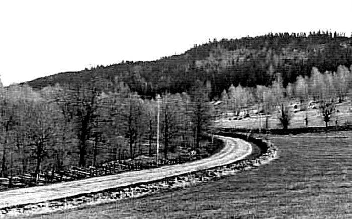 """B. 7 (6) Endast digitl bild! Vägen vid hemmanet Sten och nära Fermabron 1930-tal. En bild från 1930-talet av den """"nya vägen"""" som 1877 års väg mot Skövde i dalen mellan bergen kallades länge, innan riksväg 49 byggdes under 1950-talet. Man ser avfarten för fägatan in mot Stenslund till höger med stenmurar på vardera sidan. Läget för vägen var då ett rejält stycke mer söderut än där riksvägen sedan kom att byggas. Bäcken flyttades mot norr och en ny korsning med både Ljungstorpsväg och dess fortsättning upp mot Stenslund skapades, vilket ödelade den gamla vackra stenbron och förändrade miljön påtagligt. Riksvägens läge kom att hamna i vänster del av bilden ungefär rakt fram från betraktaren räknat. Hemmanet Sten revs 1938, då Bäckdalen 2 (Petter Lindqvists hus från 1833) revs och man använde virket från Sten för återuppbyggnad. Margit Linqvist, som idag äger det huset berättar att hennes far köpte det tomma huset i Sten 1938, det var ett timmerhus. Han rev det och transporterade stockarna till skiftet för Margits hus. Det gamla Lindqvistska huset revs också men även där återanvändes stockarna och Margits nuvarande hus blev resultatet. Margit minns detaljer när byggnationen skedde bl a en dörr med lucka som hon minns var ställd upp och ner. Spismuren i Sten stod kvar som ett skelett tills man sprängde den, kvar är en del stenar som markerar var husgrunden låg. (Berättat för Arne Sträng, 2014-02-19. Insatt av Kent Friman, 2014-02-25. Läs mer på www.ljungstorpshistoria.se!"""