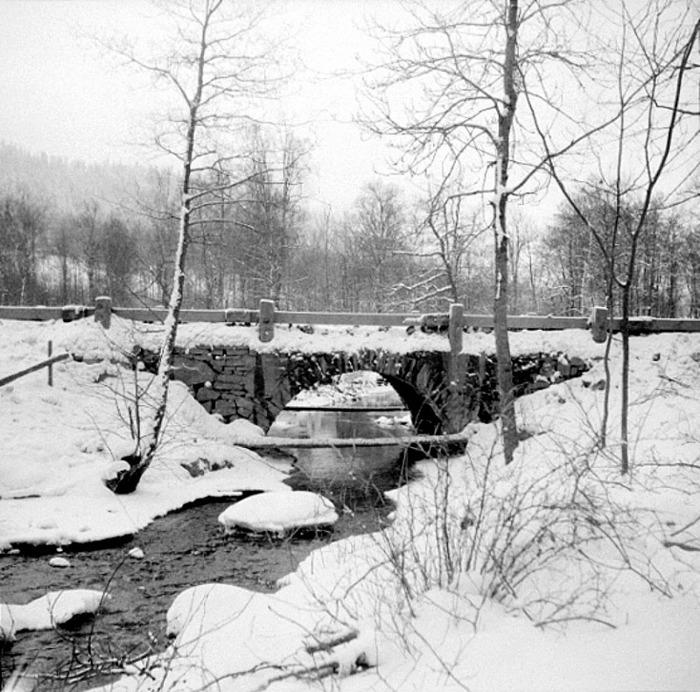 """B. 8 """"Hölltörpabrona"""" - Bron för gamla landsvägen vid Hålltorps kvarn/Tre Bäckar. Västergötlands Museum - bildarkivet/bildnummer: A145127:8 Fotograf: Nils Lann Gamla landsvägsbron ovanför Tre Bäckar. Bron var en s.k. valvbro och satt av kalksten och mycket stabil. Troligen byggd på 1860-talet. Foto från 1930-talet. Då nya väg 49 byggdes 1958 revs den och ersattes med en betongbro. Bilden tagen från platsen för den gamla kvarndammen. (Text NIls Lann). Insatt av Kent Friman, 2014-02-25. Läs mer på www.ljungstorpshistoria.se - A. 9 Tre Bäckar!"""