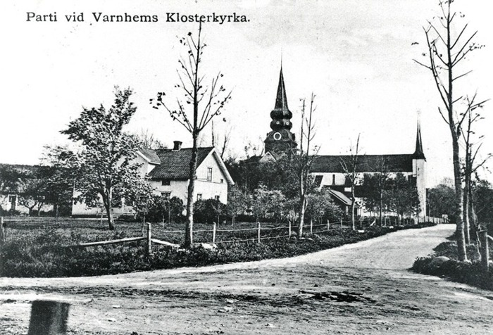"""B. 13 (2) Kyrkogatans infart 1910-1915 med Trädgården till vänster med """"gårdsstugan"""" i sin tur till vänster om boningshuset (flyttat över landsvägen under 1960-talet) och utanför bild ytterligare till vänster ligger mejeriet senare bageriet. Mellanskolan syns utmed kyrkogatan innanför staket till vänster och till höger skymtar svagt ett annat litet hus som då låg utmed Kyrkogatan ett stycke in från Folksskolan till höger (utanför bild - se ovan!). Insatt av Kent Friman, 2014-02-25. Läs mer på www.saj-banan.se!"""