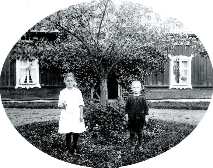 G. 9 Greta och Harald Persson framför barndomshemmet Simmesgården omkring 1920. Huset kan vara det som utflyttades från Klostrets by efter laga skiftet 1853. Insatt av Kent Friman, 2014-03-05.