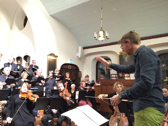 Conductor David Åberg rehearsing with choir and orchestra.