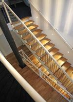 """Öppen trappa med steg i mattlackad ek. Övrigt i vitmålad furu. Underliggande vangstycken. Räcke """"Pop"""", med spjäla nr: 11 i rostfritt stål."""