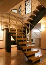 Balktrappa med vilplan och steg i klarlackad ek och svartmålad balk. Räcke 2 i rostfritt stål.