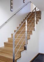 """Tät """"Z-trappa"""" med steg och sättsteg i mattlackad ek. Underliggande vangstycken i vitmålad furu. Räcke 1 i rostfritt stål."""