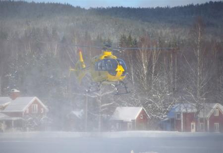 Ambulanshelikoptern lyfter i ett moln av snörök.