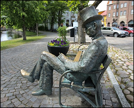 Statyn med Nils Ferlin som sitter på en bänk vid Skillerälven i centrala Filipstad. Statyn är av brons och skapad av K.G Bejemark.