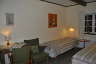 Room 5, Mundekulla. This room has 2 beds, table, chair and armchair, wardrobe and sink.