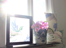 Art in window, pillows in flower textile. Window decoration by textile