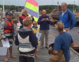 Kenned Falk avtackar seglingsledaren och brygghunden