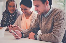 Tre studentkonsulter som testar den responsiva designen på mobilerna.