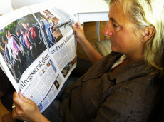 Maria Langen studerar sina Nordkoreabilder i Svenska Dagbladet. Artikeln är skriven med Sverre Sverredal - fotografen av denna bild..