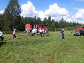 Modellrallare på besök i Hovmansbygd samtalar med sista stinsen i Hovmansbygd, Hugo Savmyr som står till vänster om vagnens gavel.