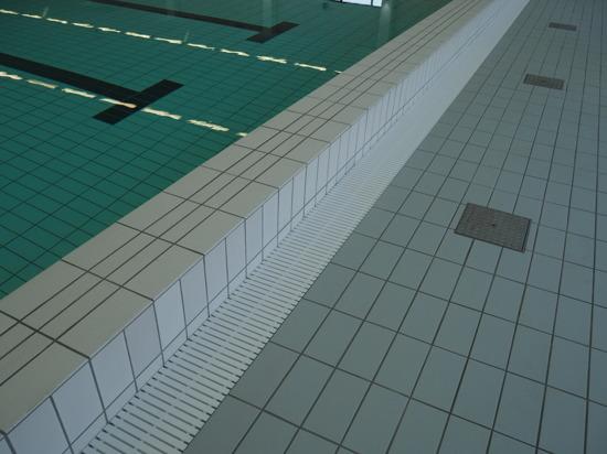 Bakom kortändan på bassängen finns en städränna med bassänggaller. Till höger linluckor för förvaring av simlinor.