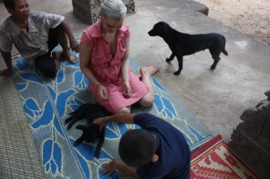 Teaching a blind boy in a temple in Cambodia how to handle the dogs the right way.