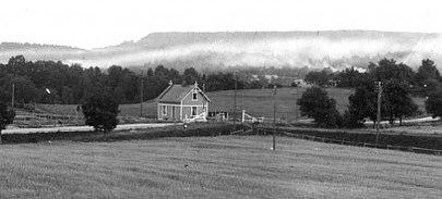 Banvaktsstugan samma år (1905) men från andra hållet med Varnhemsvägen i plankorsning, grindar och kalkrök. Delförstoring. (Skövde Stadsmuseum)