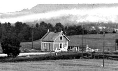Ännu närmare syns snickarglädjen på den enkla stugan, grindarna och Varnhemsvägen. Delförstoring (Skövde Stadsmuseum)
