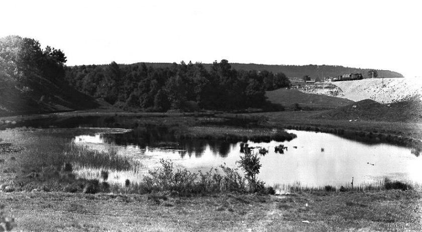 Harkessjön, sedan långt tillbaka igenfylld, låg alldeles nära SAJ-banan och en bit från Varnhemsvägens överfart. Banvaktsstugan skymtar bortom Skövde-tåget som tuffar fram 1905. (Skövde Stadsmuseum)