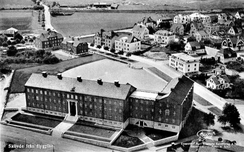 I bildens överkant ser man SAJ-banans korsning med Varnhemsvägen och de båda stugorna, ekonomibyggnaderna på det lilla industriområdet. Mäktigt bygge 1930 av Nya Läroverket. (Skövde Stadsmuseum)