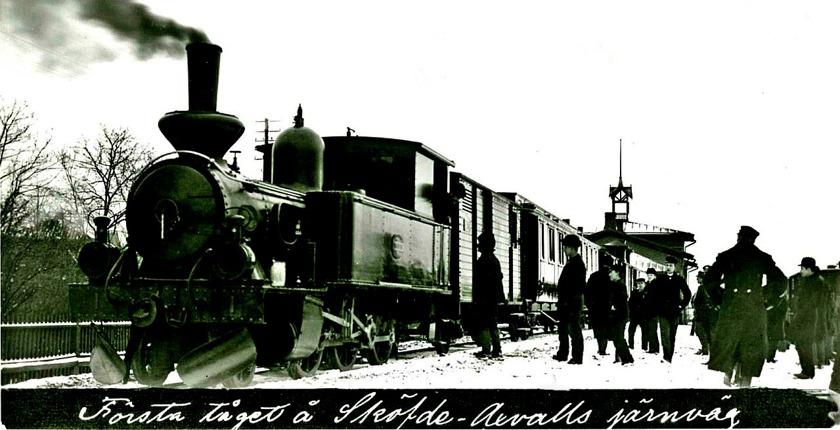 """1903-03-31 avgick det första allmänna tåget från Skövde med loket """"Sköfde"""" framför kombinerad gods- och postvagn och passagerarvagnar. Svag ostlig vind. Fortfarande vintrigt. (Skövde Stadsmuseum)"""