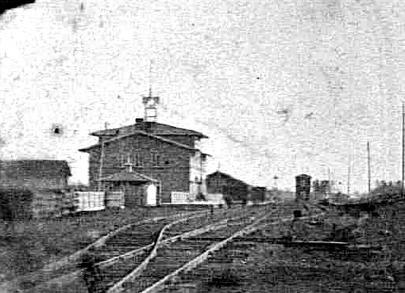 Vattenkuren skymtas t h bakom ursprungsstaket - bilden är tagen tidigast 1870 och senast 1876, då man byggde Karlsborgsbanan och utvidgade spårområdet mot Vattenkuren. (Bild Västergötlands Museum.)