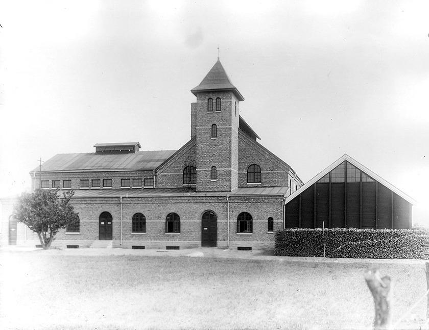Gasverket byggt 1917 -18 som ett vackert industripalats! Här har veden för tillverkningen av gas ordnats för invigningen. SAJ-banan närmaste granne västerut (t h i bild) (Skövde Stadsmuseum)