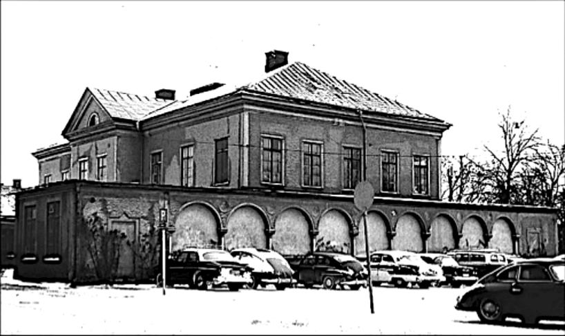"""En trist byggnadsgestalt en vintrig dag med 1960-talets bilism parkerad framför """"gårdagens"""" njutning av valvbågar, grönska, servering och fest. (Skövde Stadsmuseum)"""