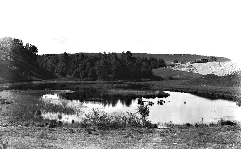 Harkessjön 1905 enligt bildtext i arkivet. Med Axevalla-tåget på väg mot Skövde som just lämnat banvaktstugan vid Varnhemsvägen (Skövde Stadsmuseum)