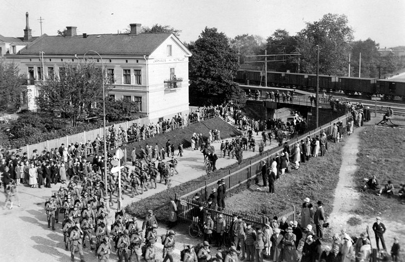 1930-tal; militären är viktig för Skövdeborna. Här stor uppslutning vid marsch under SAJ-bron. Vackert Järnvägshotell och ordnat kring gator och grönområde - SAJ's frilastområde. (Skövde Stadsmuseum)