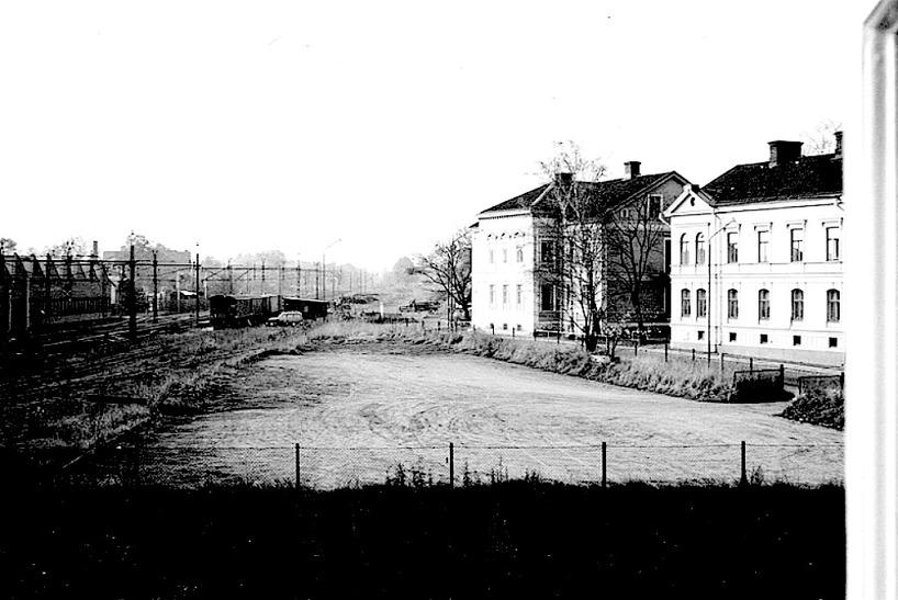 SAJ's frilastområde 1965. Området användes för anra ändamål. Länge tillfällig parkering för Volvo Penta-arbetare.  Flickskolan och lokförare Dahlins hus t h. Stoppbocken syns. (Skövde Stadsmuseum)