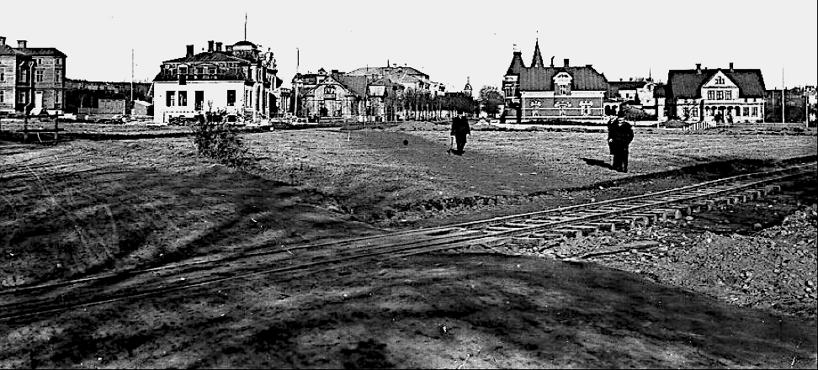 1903 nära nuv. Vasaplan. Färdigt genomgångsspår mot Axvall klart. SAJ's södra bangårdsdel saknas ännu på bilden och mycket schaktning återstår. Drottninggat 18 under uppförande. (Skövde Stadsmuseum)