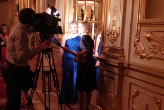 Katharina i blå klänning under balen på Grand Hôtel vid intervju av rysk tv.