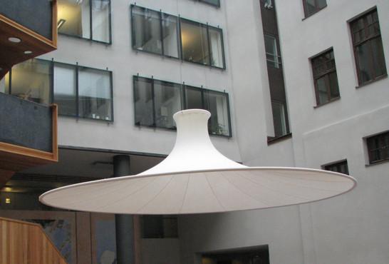 UTMANING:   Ljudet studsade kraftigt upp och ner på en innergård i Stockholm. LÖSNING: Med upphängning av vår ljudabsorbent Tratti, 5 meter i diameter, förbättrade vi ljudmiljön avsevärt.