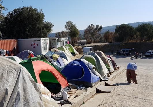 Foto från okt 2019: tältsamling utanför murarna till Morias flyktingläger på Lesbos.  Observera lastpallarna som lagts under tälten för att undvika regnvattnet som ibland forsade nedför sluttningen. I barackerna till vänster bedrev volontärer rådgivning kring medicinska frågor och asylärenden.  Allt är nu nedbrunnet.  Foto: Lisa Norgren Benedictsson