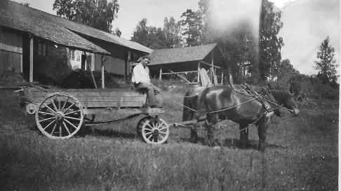 Erik Djuffält som kusk på gödselspridaren. Bilden sannolikt på Lundaby där Erik var dräng mellan 1930 och 1934.