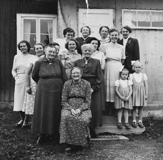 Ida fyller 70 år 1954. I förgunden Ida Karlsson, född Larsdotter. Grannarna uppvaktar. Fr v Emmy på Nyback, Valborg i Nystuga, Beda i Sydstuga, okänd, Olga på Ollesberg, Sara på Ollesberg, Helga på Ös