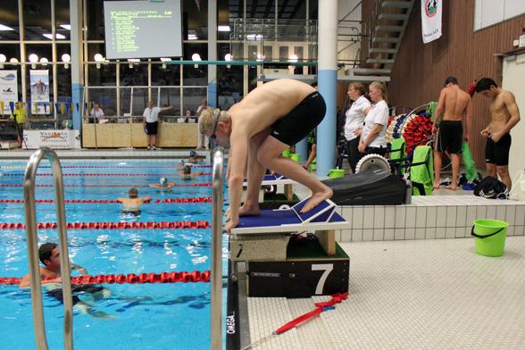 Full aktivitet på startbryggan. Fyra lager med olika fokus. Simmare i vattnet, på pallarna. Funktionärer där bakom och längst bak laddande simmare som startar i nästa heat.
