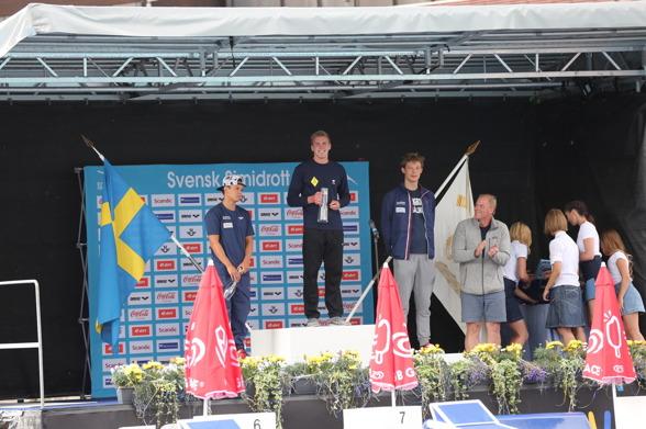 Prisutdelning på 200m bröstsim herrjuniorer. Överst på pallen Carl Arvidsson och prisutdelare - i grått pappa Pär Arvidsson, OS-guldmedaljör på 100m fjärilsim 1980.