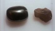 Svart cabochonslipad enstatit med kattögaeffekt och en brun rå translusent bit.
