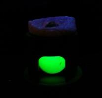 På bilden en diamant som undersöks genom att belysas med kortvågigt UV-ljus. Diamanten ligger med bordet nedåt och påminner om en svart pyramid. Det gröna skenet avslöjar dock att diamanten släpper igenom kortvågigt UV-ljus vilket betyder att den kan vara syntetisk. Som synes på bilden fluorescerar inte diamanten under test för kortvågigt UV-ljus.  UV-ljus används alltså på olika vis för att identifiera diamanter som kan vara syntetiska